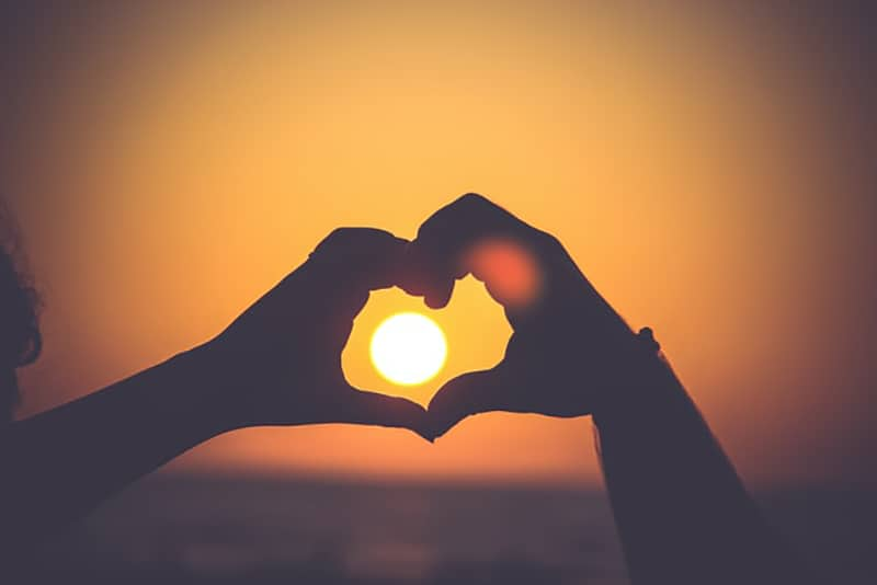 two persons made a shape of heart with hands during sunset