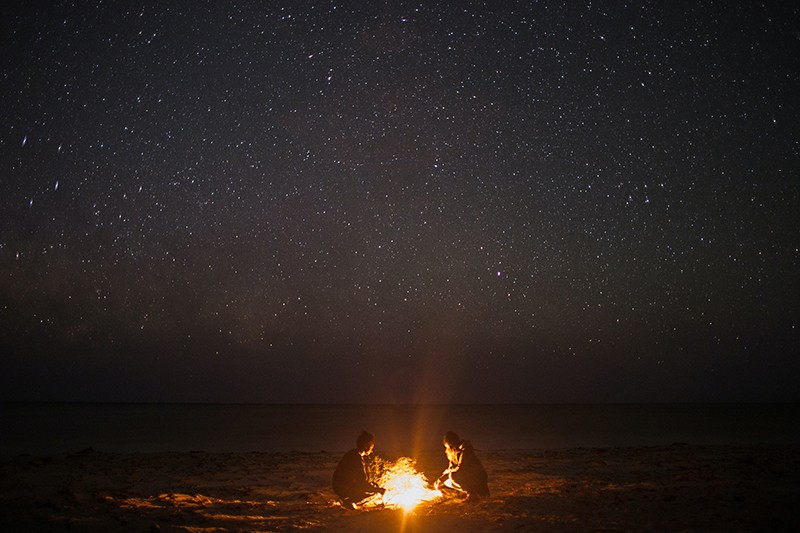 two persons sitting near bonfire on the coast at night