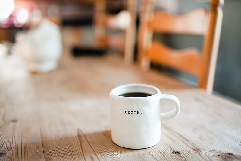 white ceramic mug with message Begin which standing on wooden table