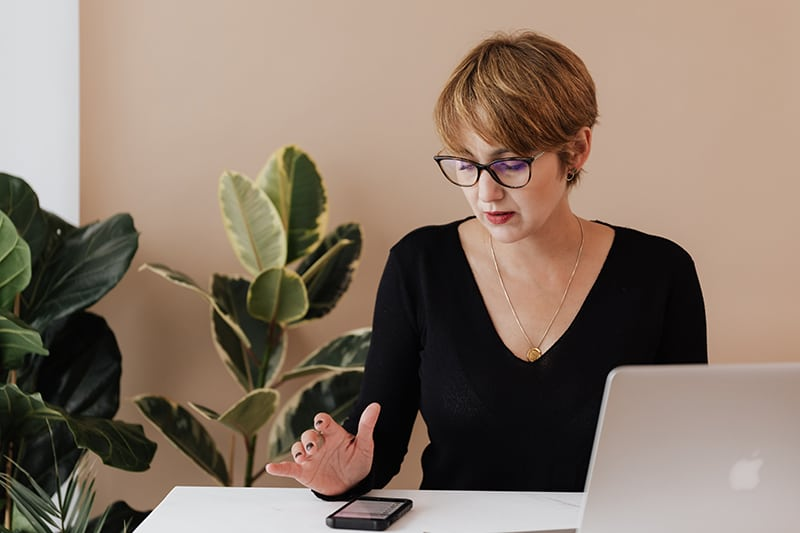 woman checking her phone while sitting in front of laptop