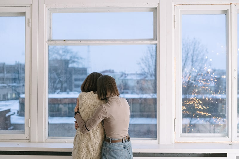 woman consoling her female friend hugging her near the window