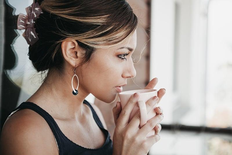 woman drinking coffee looking pensive