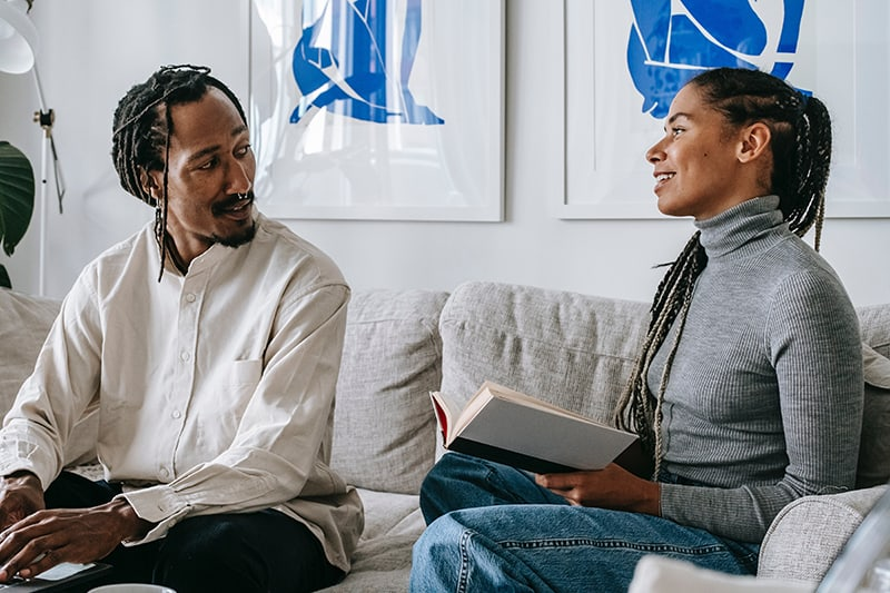 woman holding a book and talking with a man sitting on the couch beside her