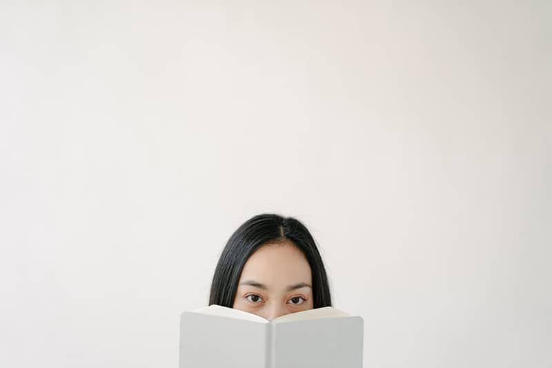 woman holding book and covering mouth with it