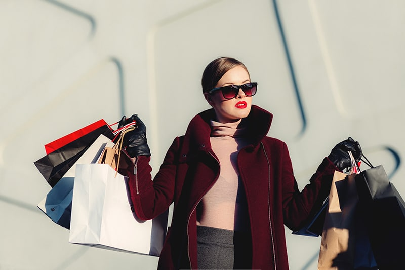 woman wearing sunglasses and holding shopping bags