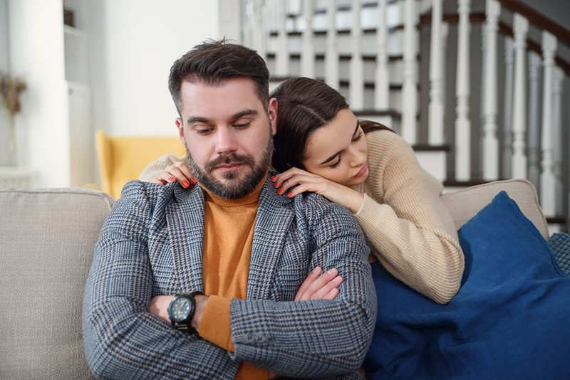 woman hugging upset boyfriend sitting on the couch
