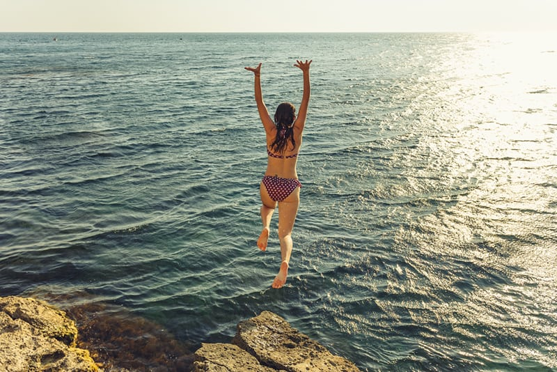 woman jumping in the sea from the cliff