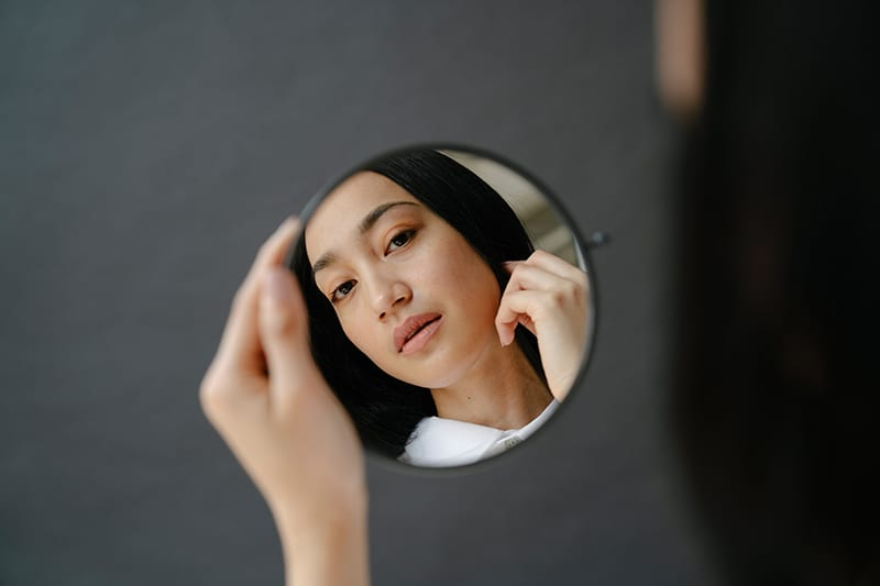 woman looking at mirror holding it in her hand