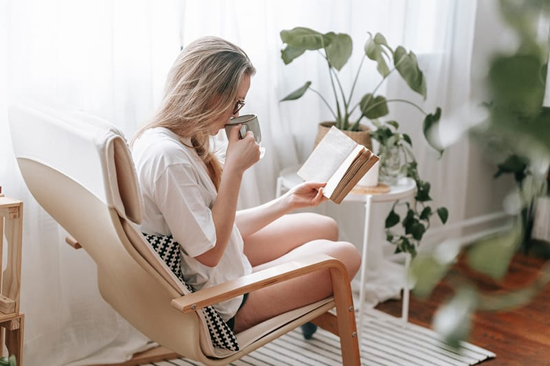 woman reading a book and drinking coffee at home