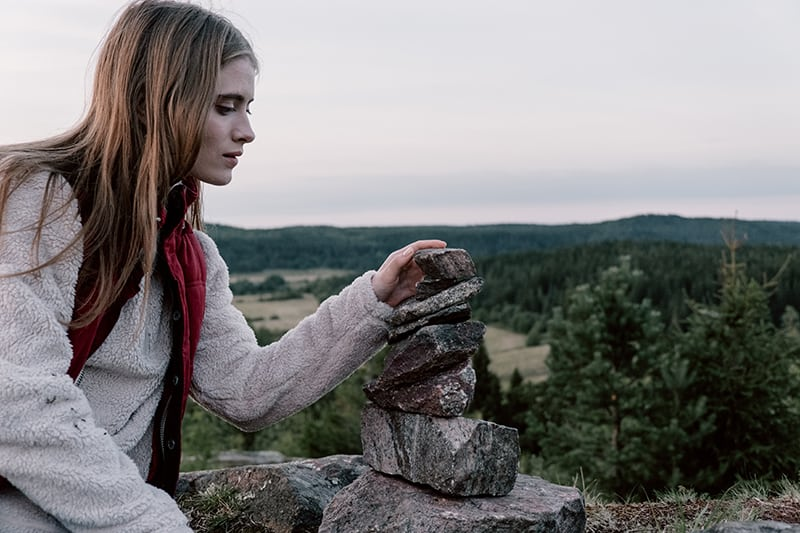 woman stacking rocks in the mountain