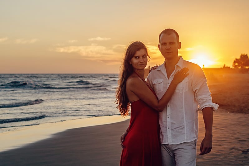 woman standing beside man on the seashore during sunset