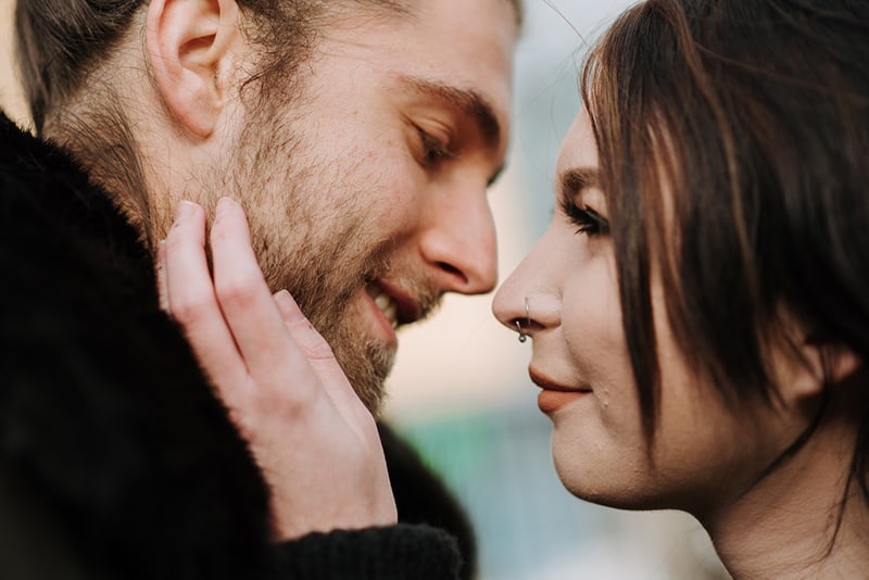 woman touching a face of smiling boyfriend about to kiss her