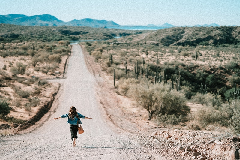 woman walking on dirt road spreading her arms