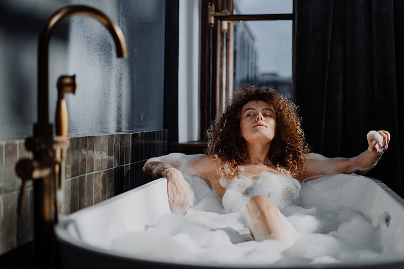 woman with eyes closed in bathtub relaxing