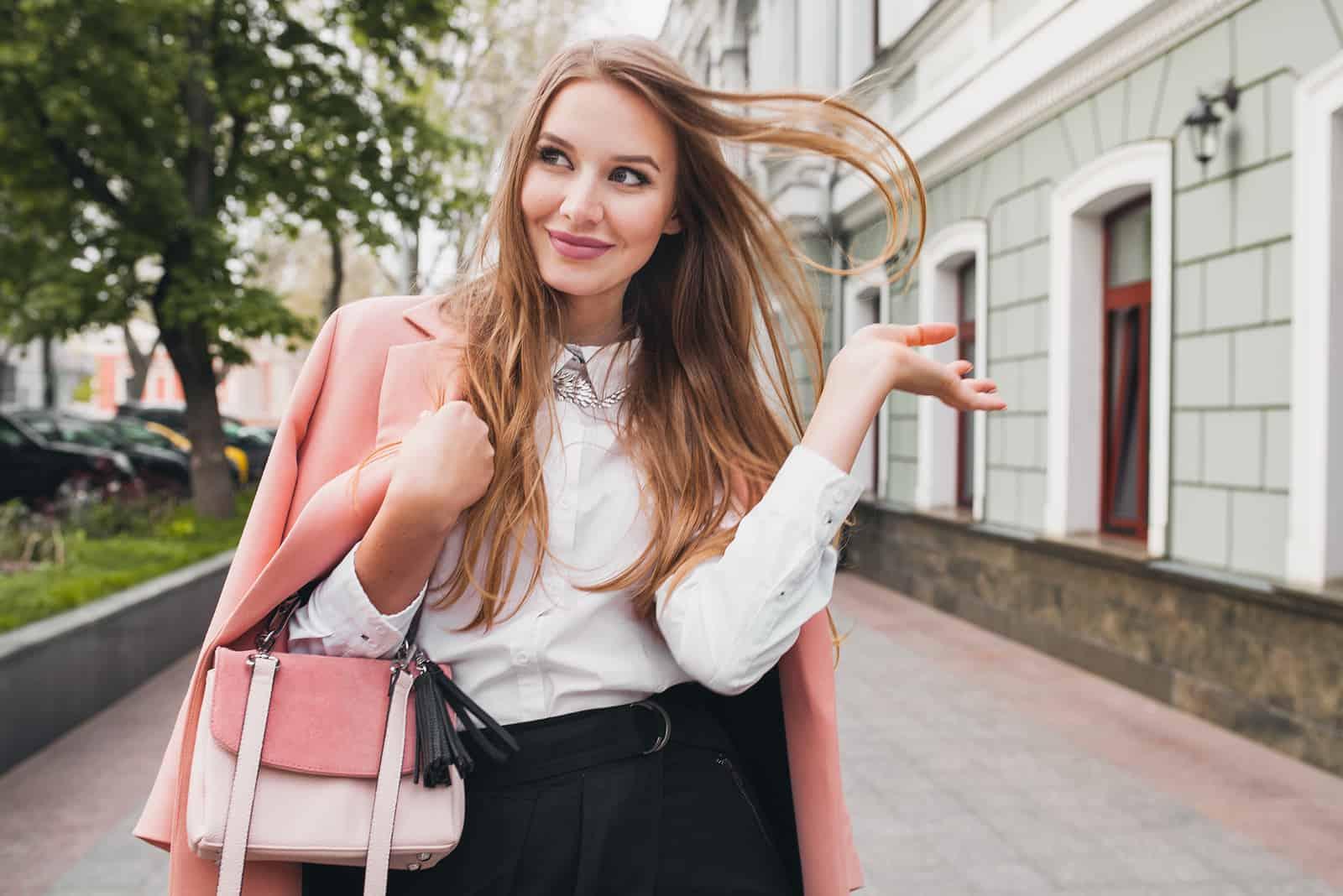 young beautiful stylish woman walking in pink coat