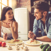a man and a woman sit in the kitchen and eat