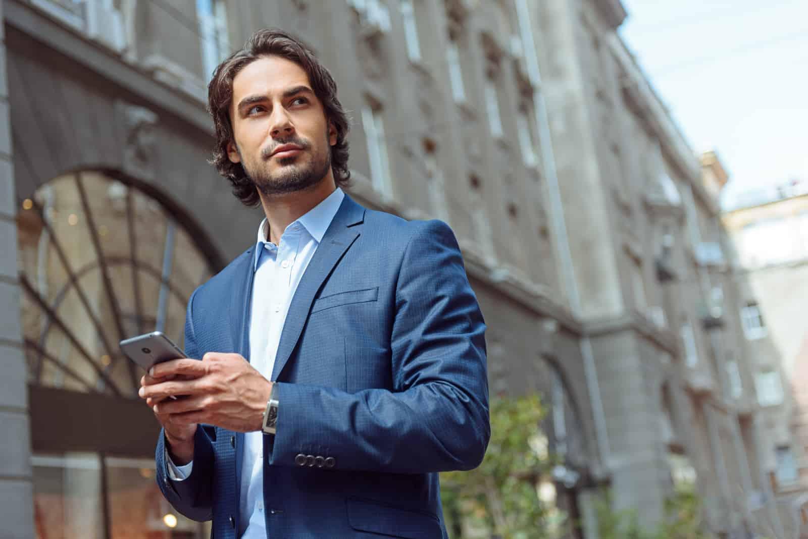 Cheerful businessman holding telephone