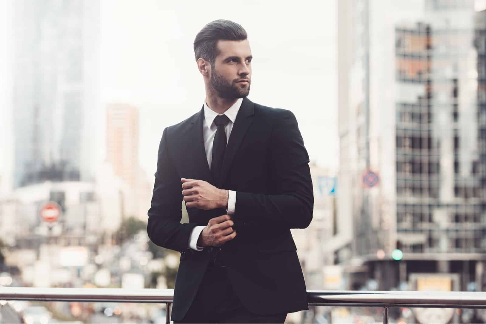 Confident young man in full suit adjusting his sleeve