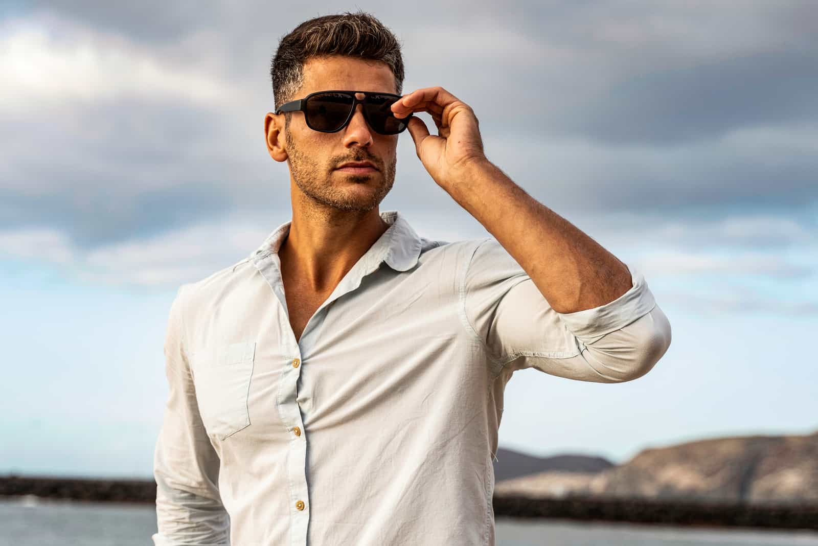 Gorgeous stylish man wearing fashionable shirt and sunglasses