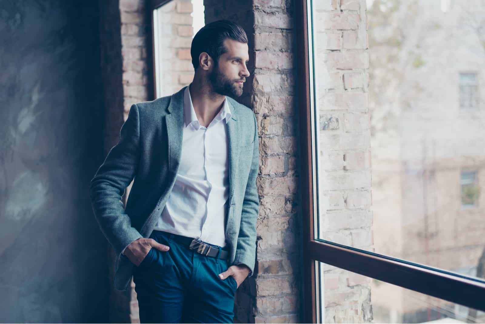 Stylish young bearded man is standing near the window