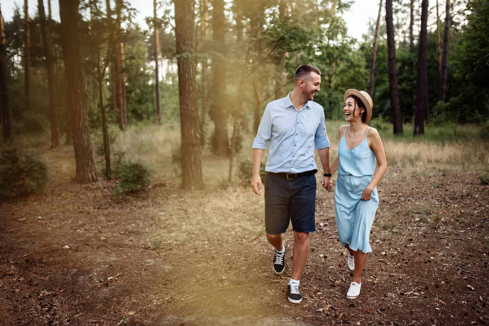 a smiling loving couple sets through the park