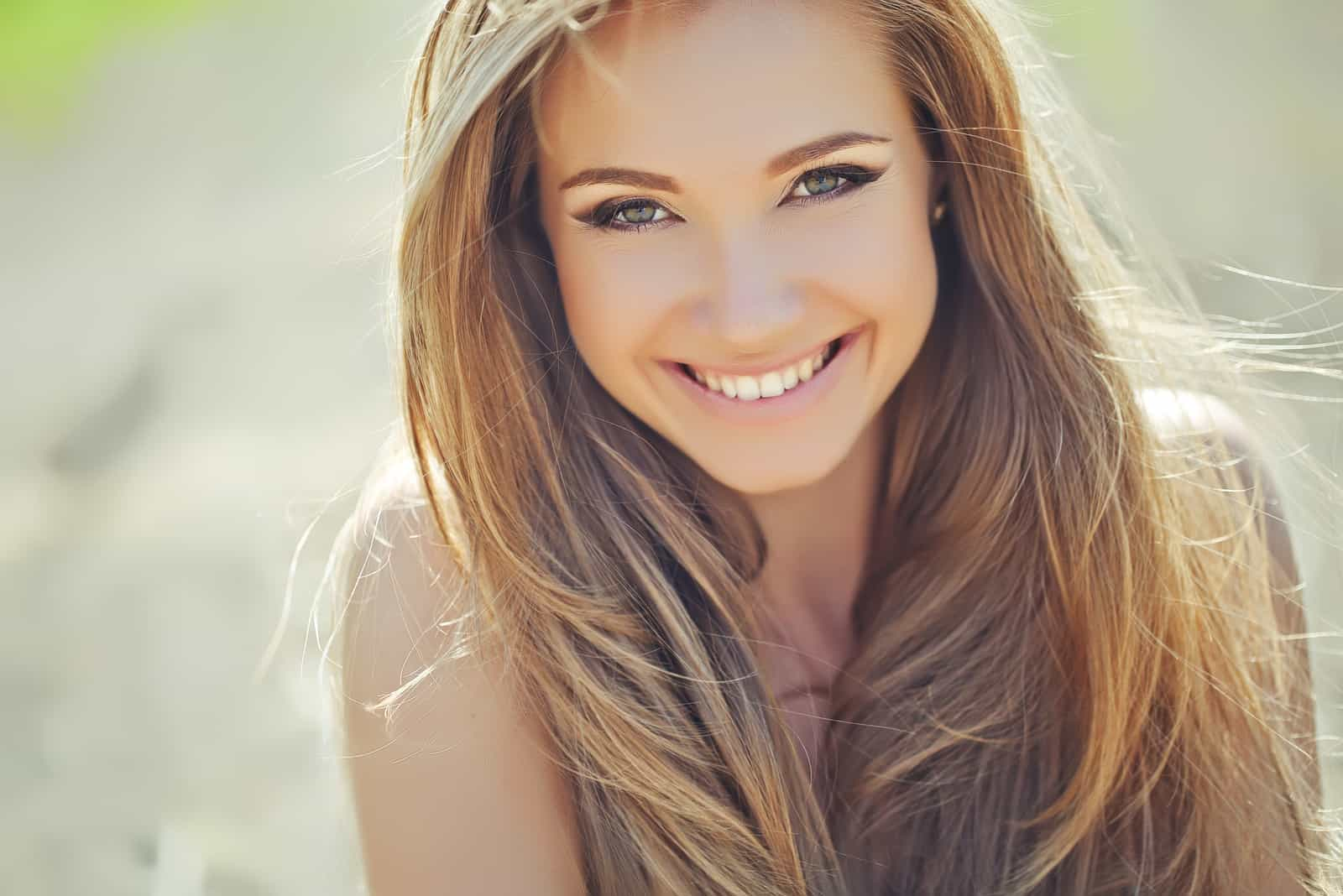 a beautiful smiling woman with long brown hair