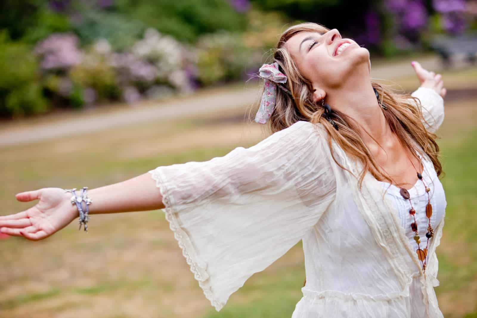 a beautiful woman in a white dress stands with her arms outstretched