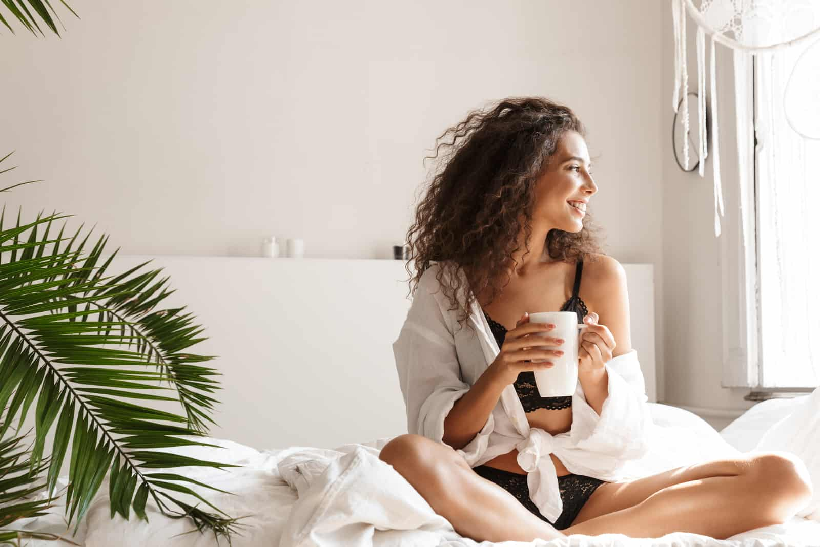 a beautiful woman with frizzy hair sits on the bed and drinks coffee