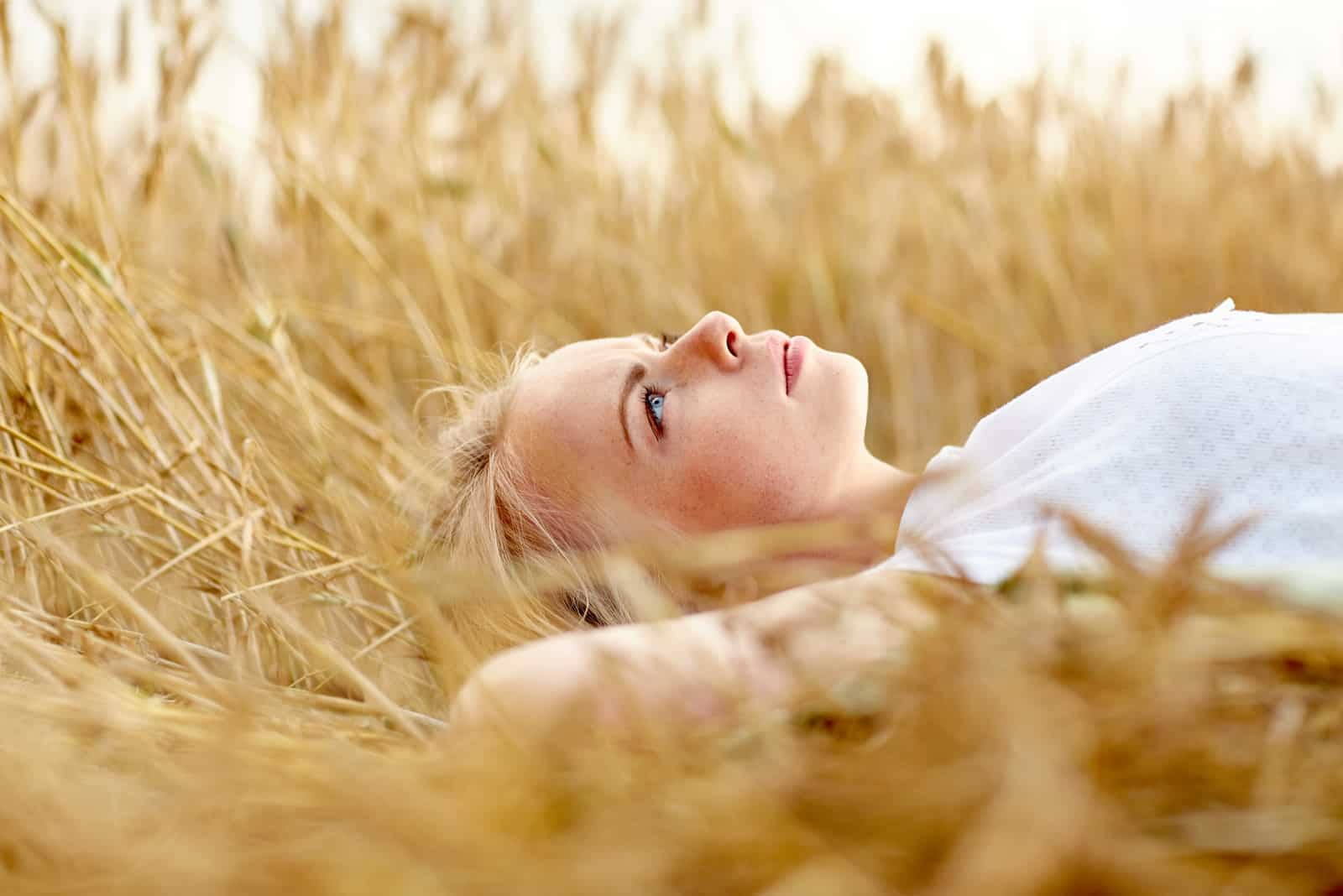a blonde-haired woman lies in a field of wheat