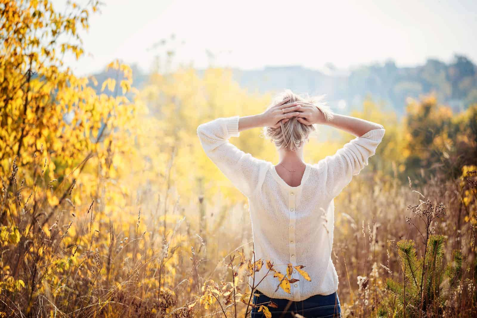 a blonde-haired woman standing in a field put her hands on the back of her head
