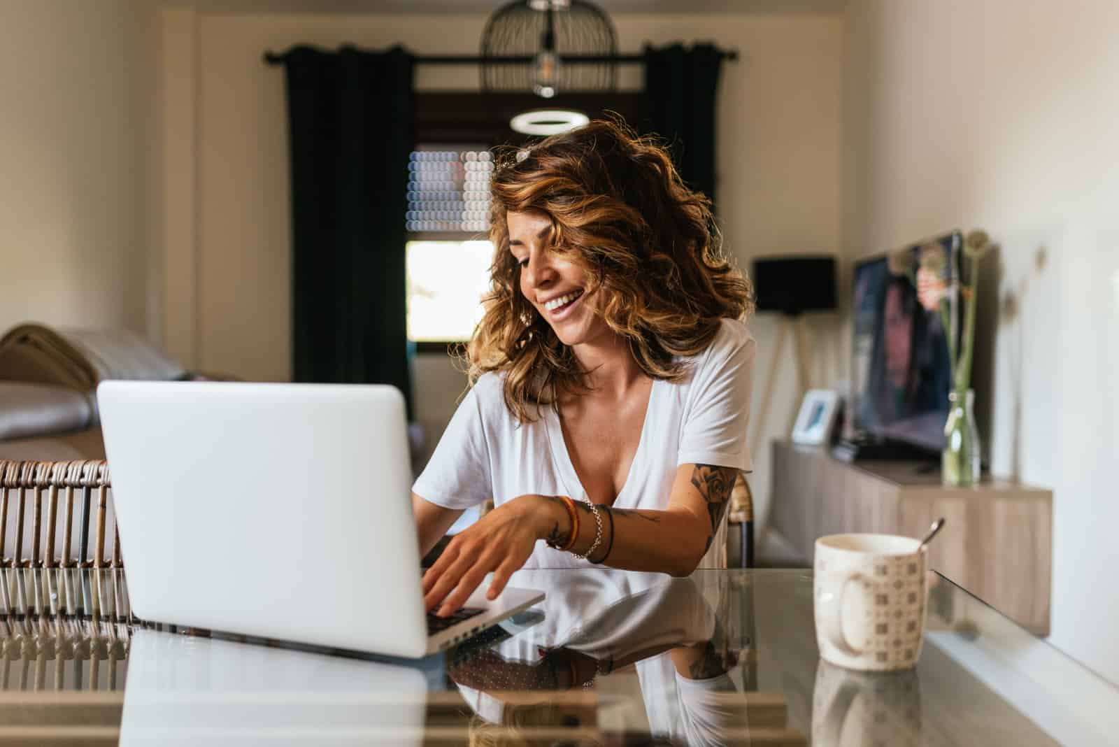 a brown haired woman sitting behind a laptop