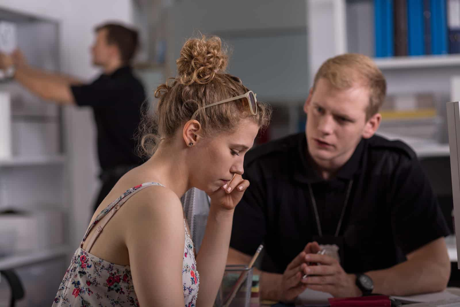 a downcast woman talks to a man