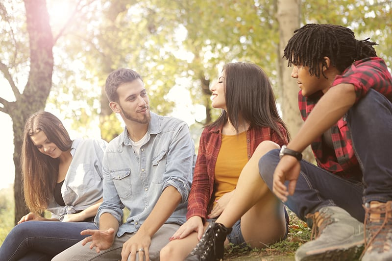 a group of friends talking while sitting in the park