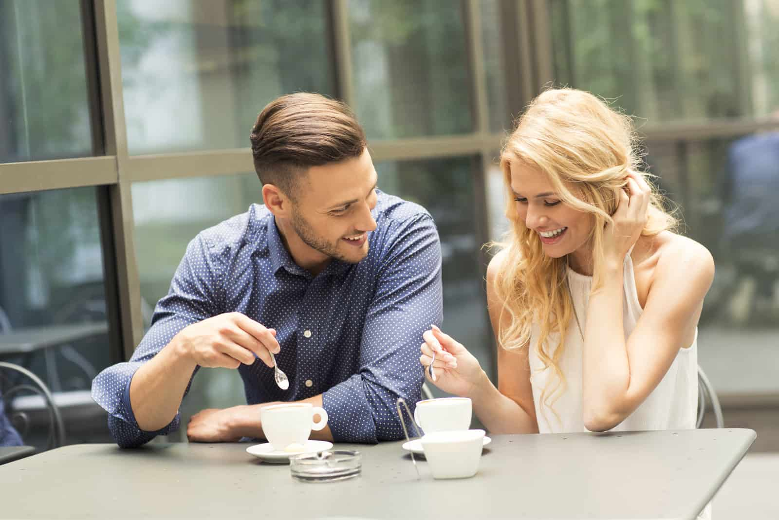 a man and a woman are sitting outdoors talking over coffee