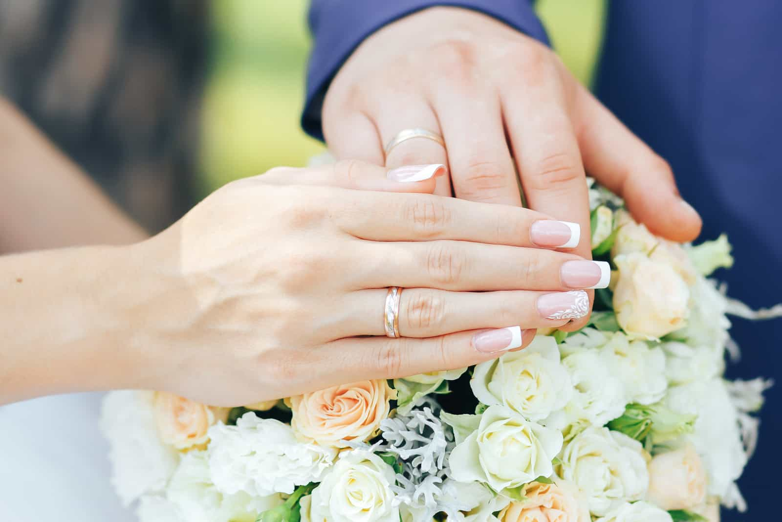 a man and a woman held out their hands with wedding rings