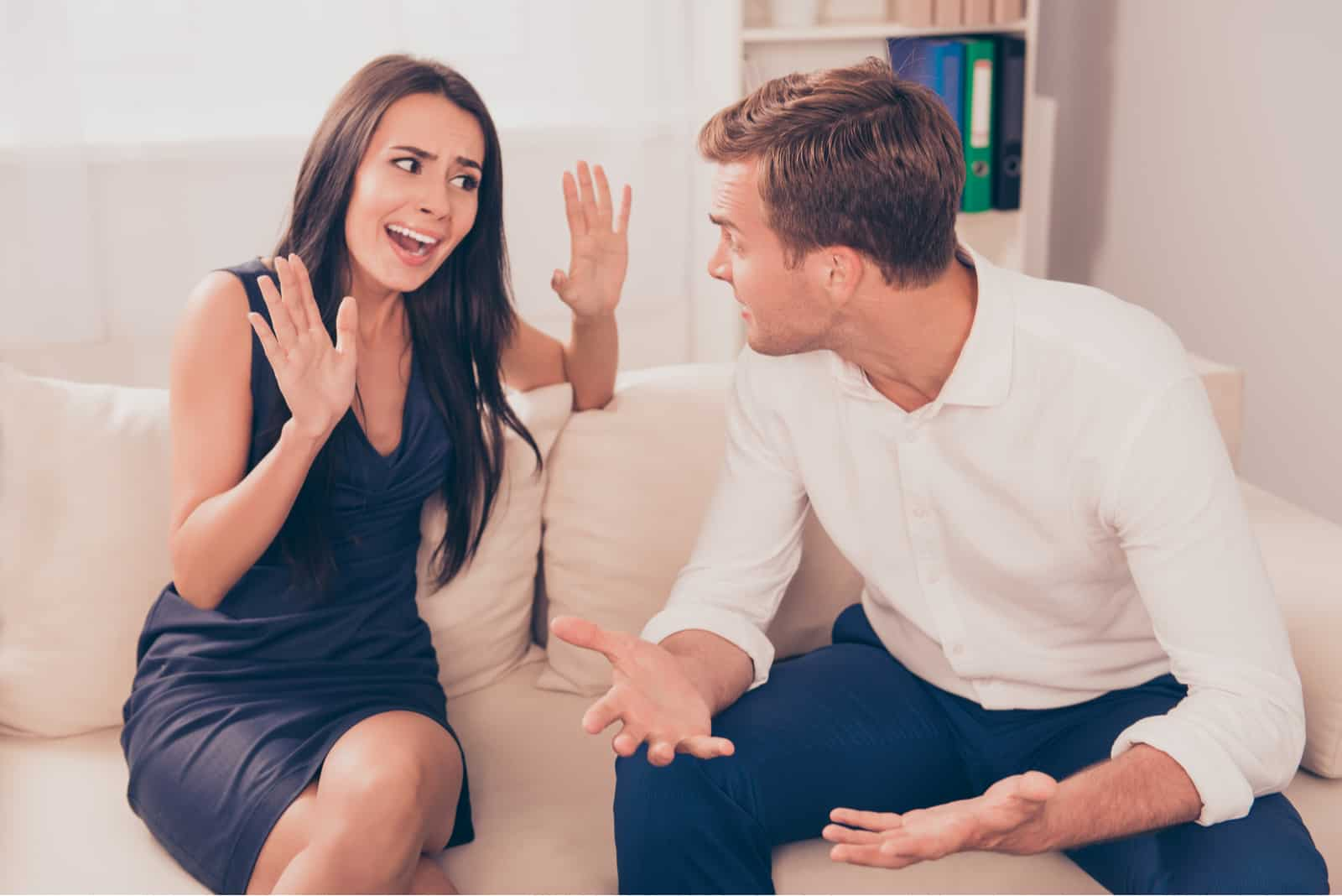 a man and a woman sit on the couch and quarrel