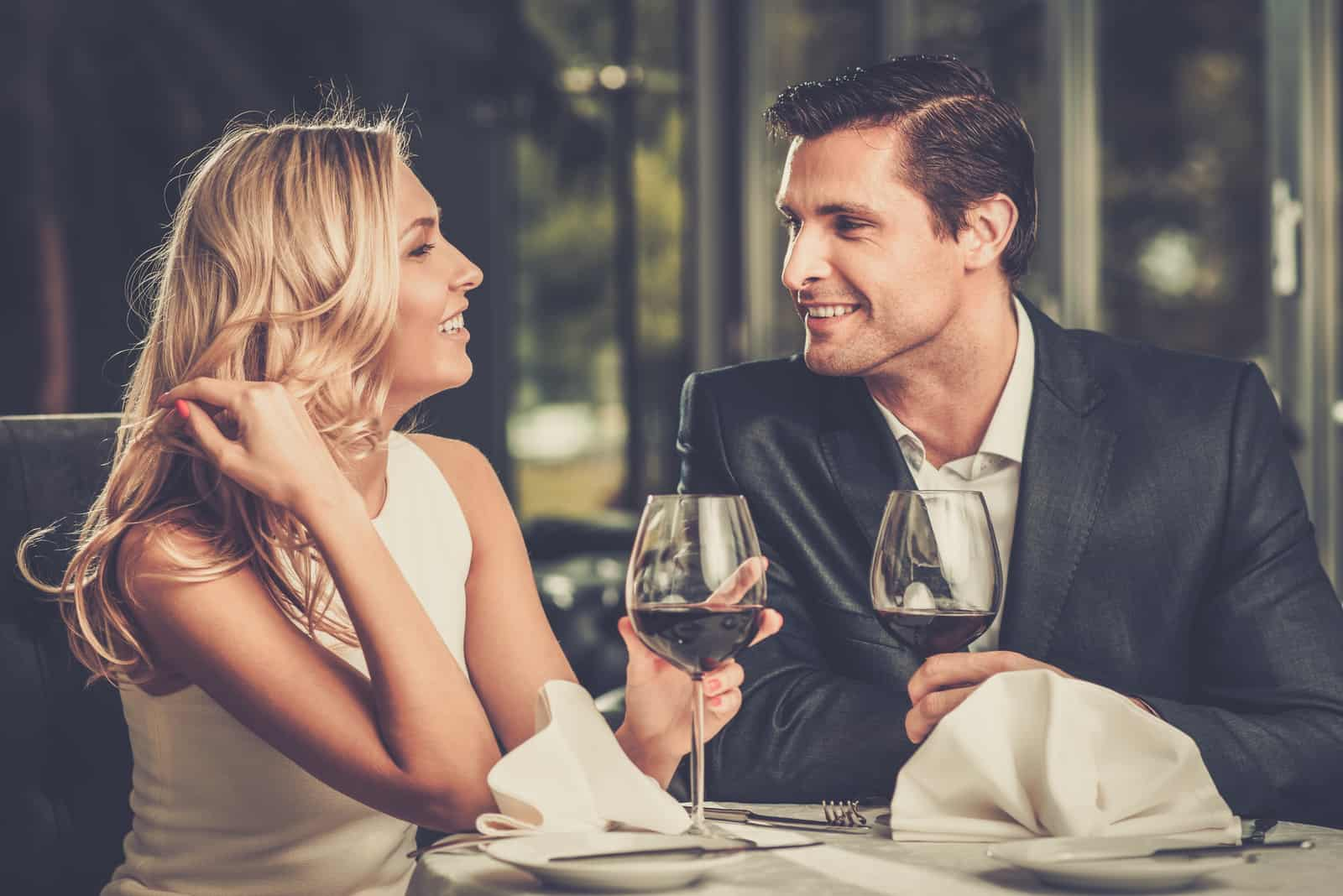 a man and a woman sitting at a table with wine talking