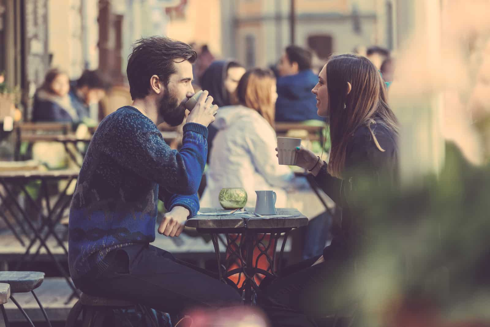 a man and a woman sitting outdoors having coffee talking