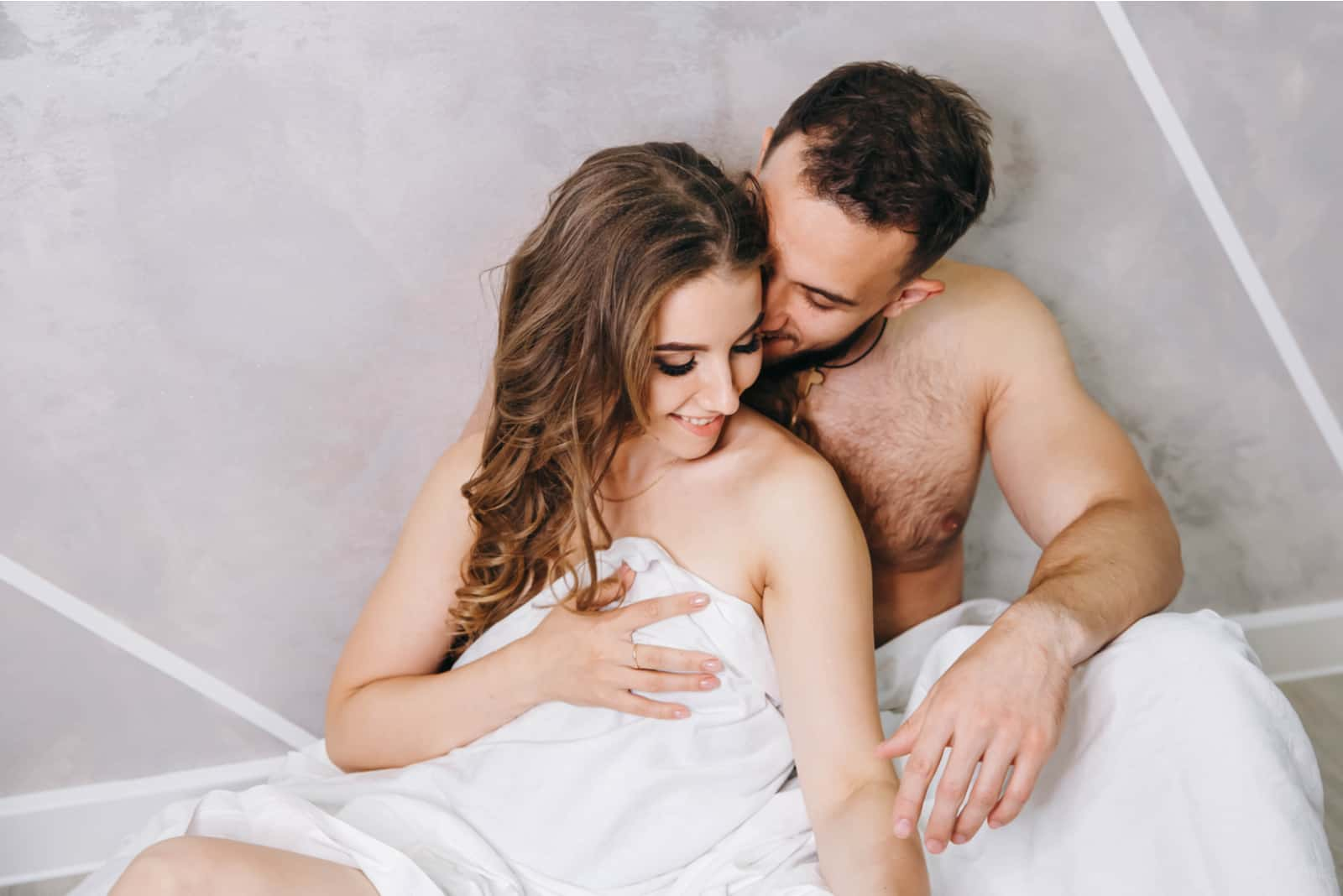 a man caresses a woman in bed