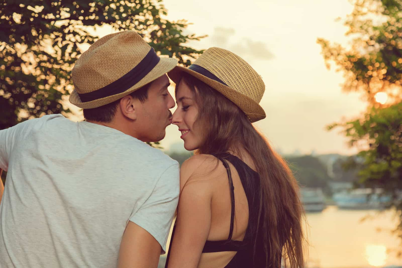 a man kisses a woman on the nose as they sit