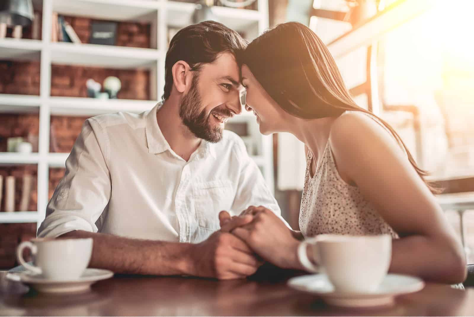a smiling loving couple cuddles in a cafe