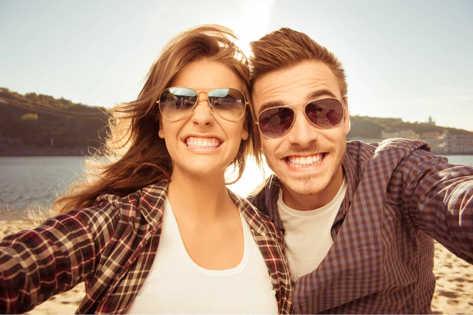 a smiling man and woman are photographed with glasses on their heads