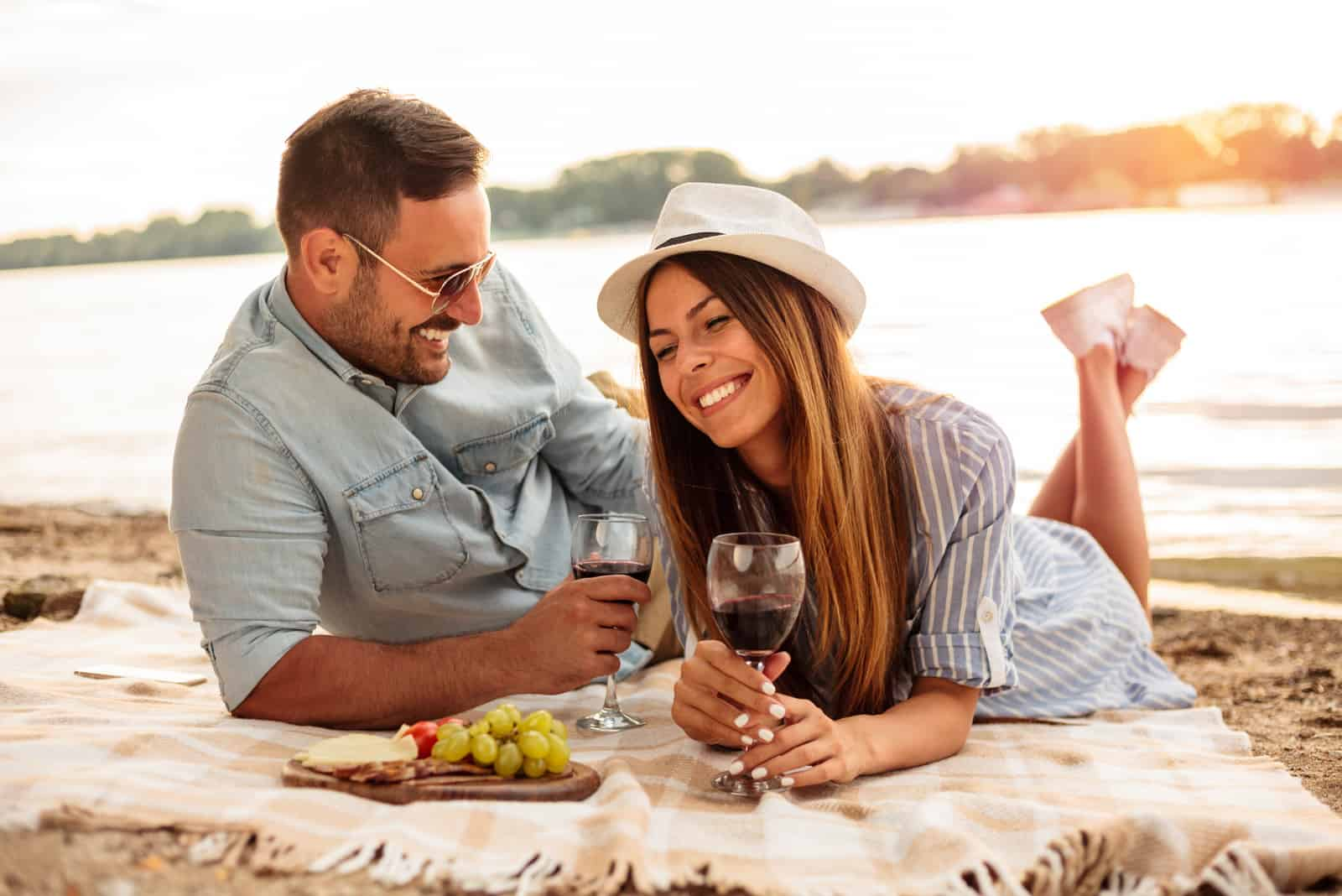 a smiling man and woman lie on the beach and drink wine