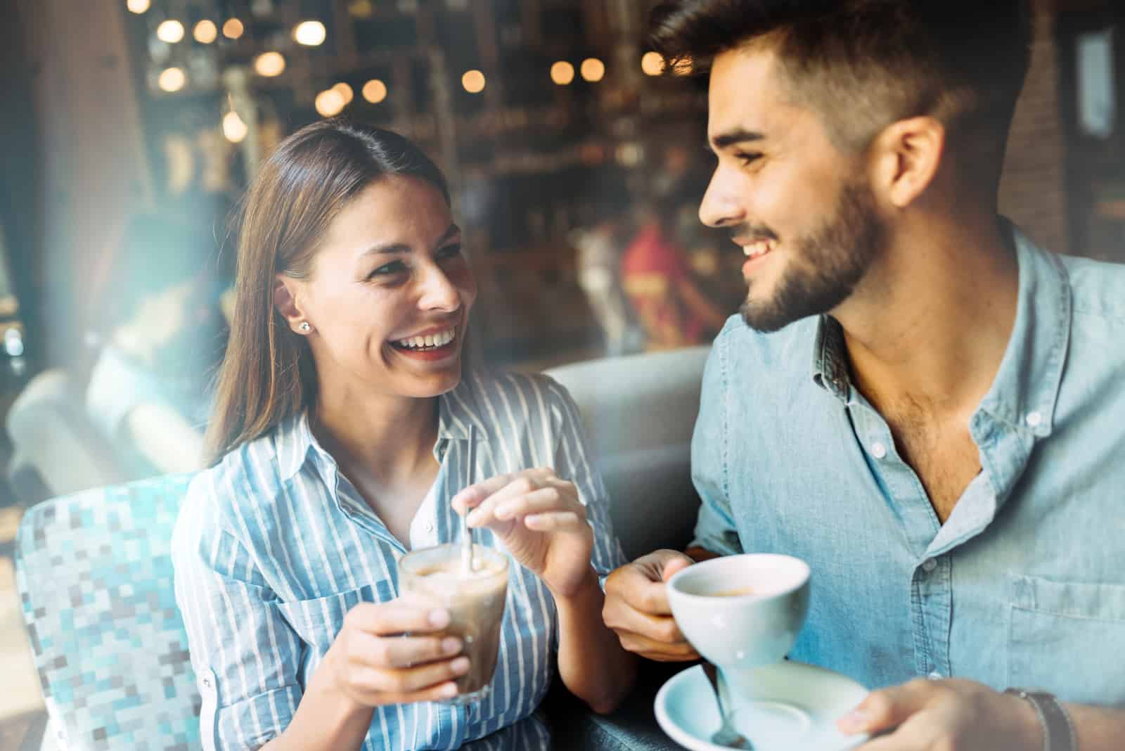 a smiling man and woman sitting at a table drinking coffee