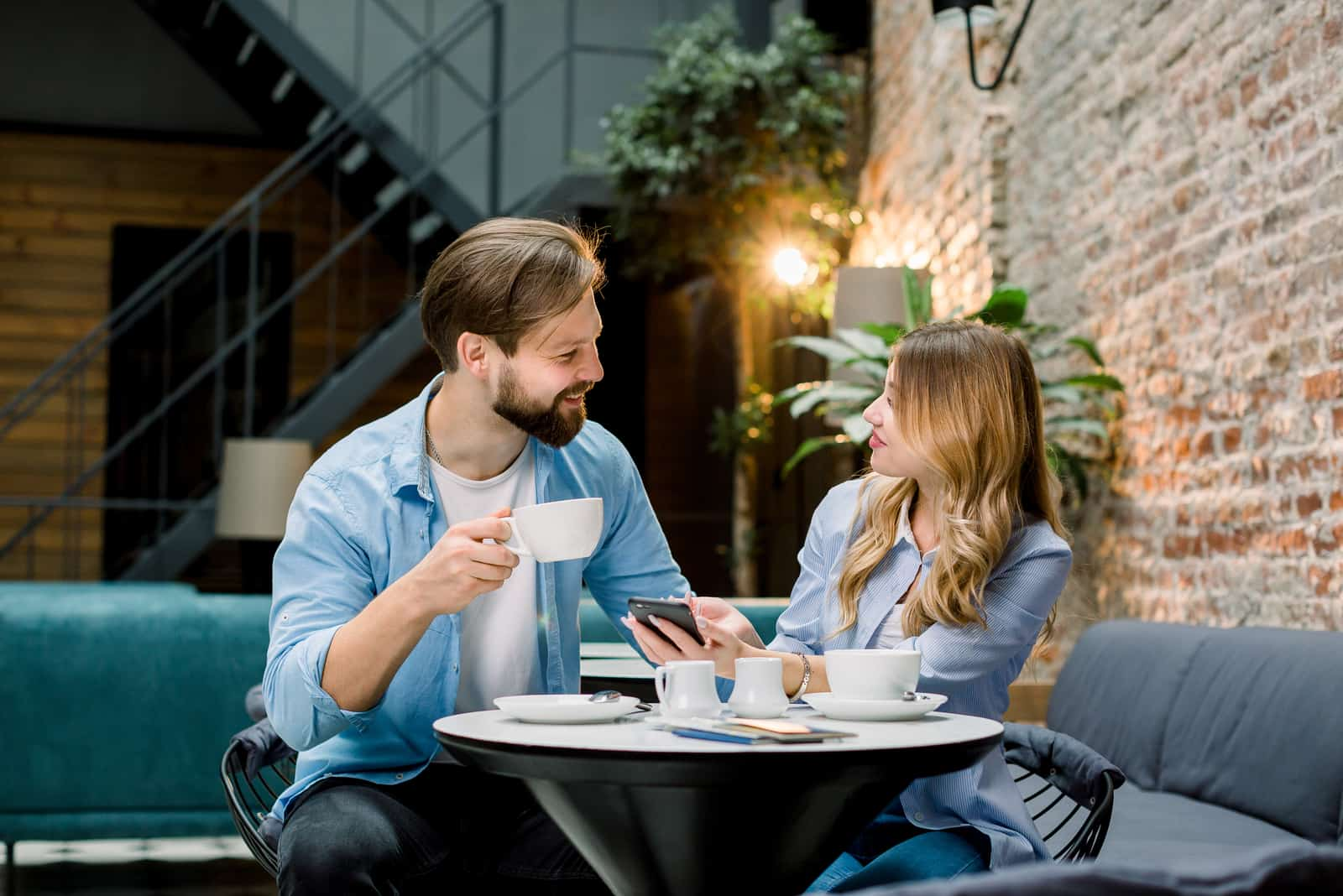 a smiling man and woman sitting at a table having coffee talking
