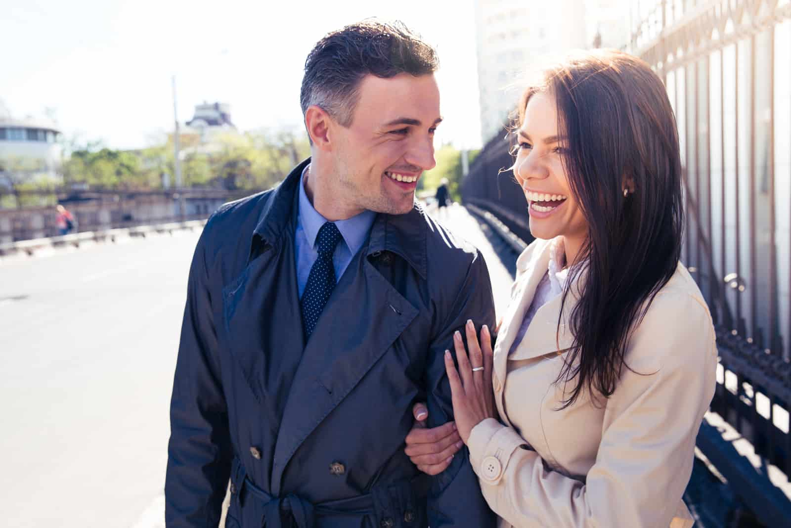 a smiling man and woman stand in the street