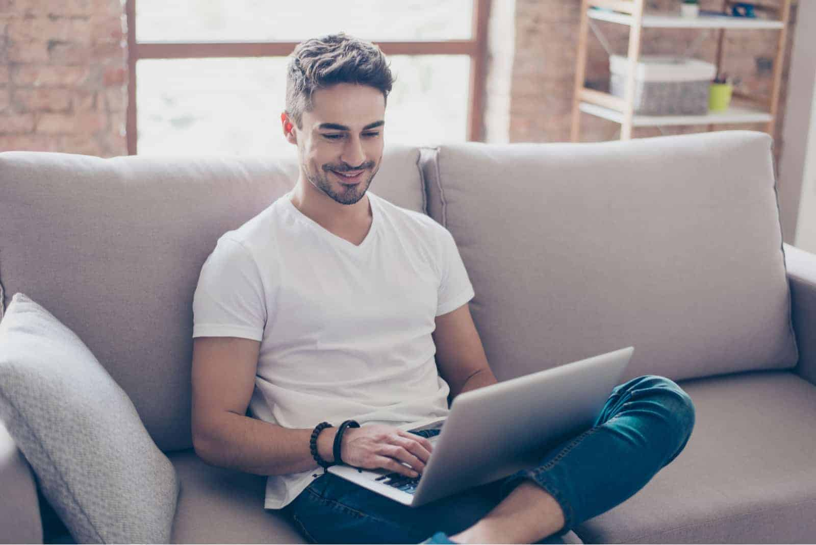 a smiling man sitting on the couch and typing on a laptop