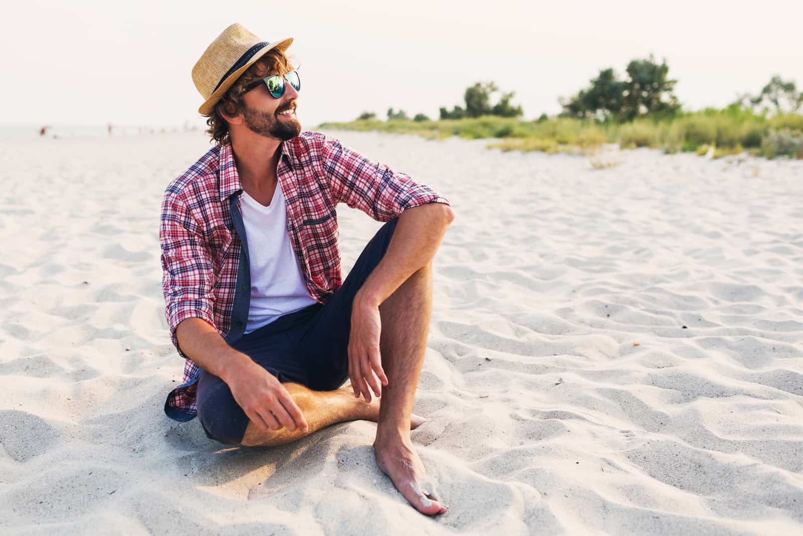 a smiling man with a hat on his head is sitting on the beach