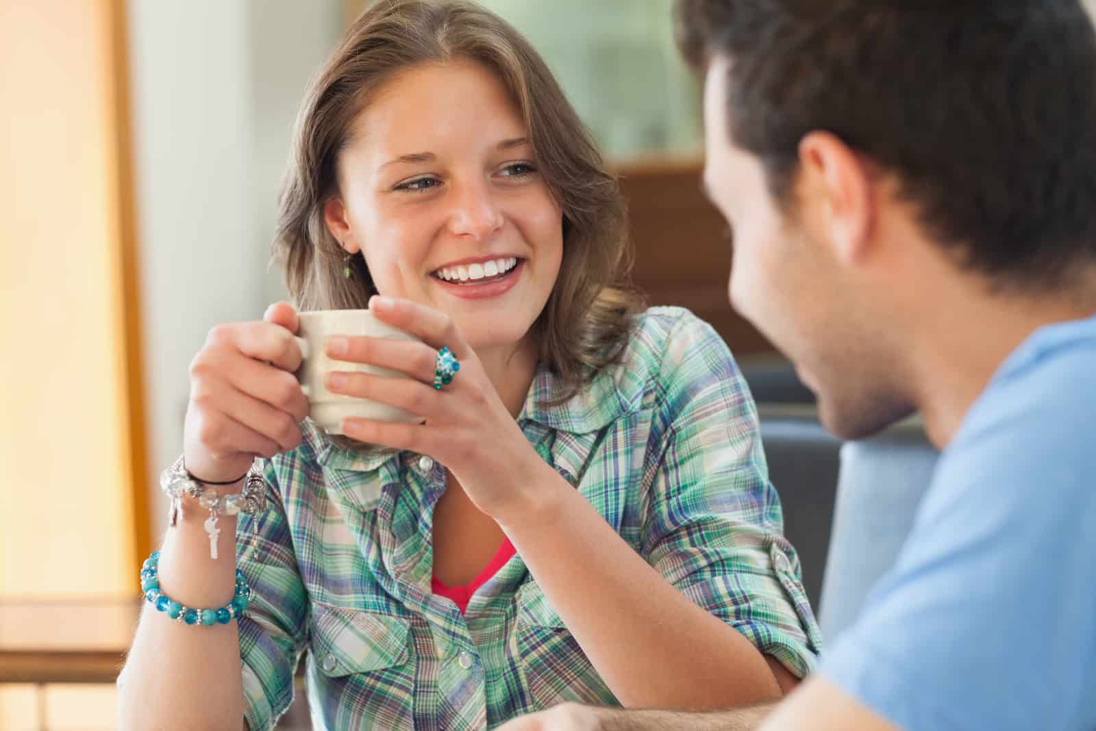 a smiling woman drinking coffee with a man and laughing