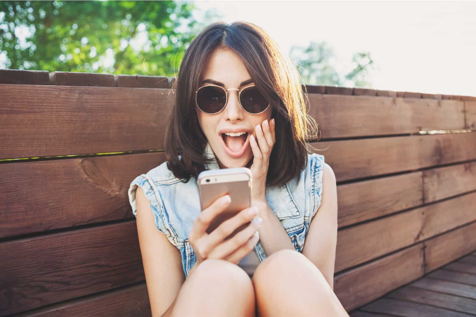 a smiling woman with glasses takes a picture on the phone